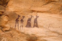 Tarssed Jebest, Algeria. Line of four maroon figures face forwards. Two men at left with very thin spike heads short skirts Two women at right with very thin spike heads. #africanrockart http://africanrockart.org