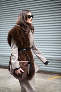 This glossy-haired Fashion Week showgoer demonstrates the chicest way to style a fur scarf—cinched with a skinny belt.