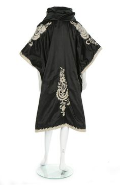 A rare Lucile black satin evening cape, circa 1914. un-labelled, embroidered in white wool and angora with Indian inspired foliate boteh motifs, raised, pleated collar to frame the face, no fastenings, side slits for the arms, lined in black chiffon