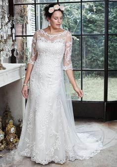 Verina wedding dress by Maggie Sottero |  A dramatic illusion lace back and illusion sleeves adorn this hand-embellished sheath gown, glimmering with metallic lace appliqués and embroidered with beading drifting from shoulder to floor-skimming hem. A delicate scalloped hemline completes the look. Finished with pearl button over zipper back closure.