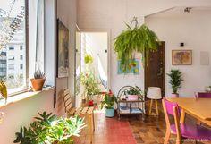 Sala de estar integrada com muitas plantas, piso de ladrilhos e peças garimpadas