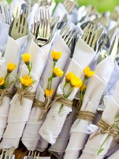 Cubiertos en un rulo con servilletas y flores