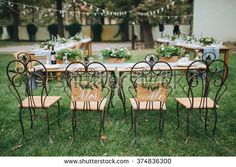 Wedding. Banquet. Chairs and honeymooners table decorated with candles, served with cutlery and crockery and covered with a tablecloth. The table stands on a green lawn in the backyard banquet area