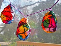 So easy!  Cut 12 inch pieces of yarn, soak in white glue.  Wrap around a water balloon, steadied by a cup to hold in place.  Using two parts glue to one part water, place tissue pieces on balloon and brush on glue mixture.  One layer is sufficient.  Allow to dry for 24 hours, pop balloons and hang!