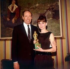 """March 13, 1964, Audrey Hepburn, with her husband Mel Ferrer, holding the David di Donatello award, photographed by Angelo Frontoni during a cocktail party at the Palazzo del Quirinale in Rome (Italy), held for the movie personalities who were awarded with the David of Donatello (the Italian equivalent of anOscar). Audrey had won Best Foreign Actress for """"Breakfast at Tiffany's"""" in 1962. Audrey was wearing diamond earrings from Cartier (which she purchased in 1959)."""