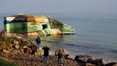 ARTE E HISTORIA. La gente posa frente a un búnker sobre el mar utilizado durante la Segunda Guerra Mundial, que fue pintado por los artistas Baby K y Blesea, el 20 de diciembre de 2017 en Reville, en el noroeste de Francia. (AFP / CHARLY...