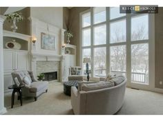 Stay cozy by the fireplace in this living room with vaulted ceilings and large windows!