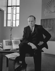Photograph of Marshall McLuhan posing at table with books, January 21, 1967, by Yousuf Karsh. © The Estate of Yousuf Karsh. All Rights Reserved