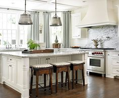 Planked walls and a coffered ceiling add character to this kitchen. A spacious marble-topped island is complete with furniture-style details and a trio of wood stools. Heavily veined marble acts as a backsplash and the accent color in this classic white kitchen and adjacent breakfast nook./