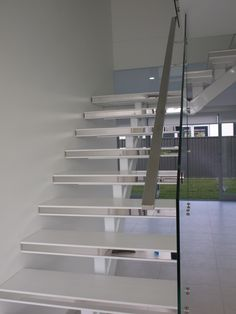 Modern Steel mono string Staircase with corian treads and glass balustrading with stainless steel handrail by Sydney Staircase Builders.