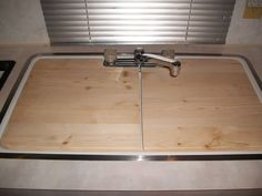 Just create your own sink cover by using a cardboard template and make from wood. Measure, template, cut, sand, finish, DONE. Better yet, instead of finishing with stain and/or varnish, use a food safe cutting board oil to make it a productive cover that doubles as a cutting board.
