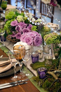A centerpiece of branches, moss, crystals, calla lilies  and purple roses tops a long wooden table.