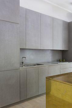 Materialen betong, valchromat och kalksten går igen i hela inredningen med en guldfärgad kontrast i de mässingklädda förvaringslösningarna.