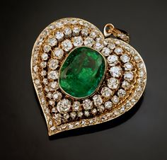 An Antique Victorian Era Emerald and Diamond Heart Shaped Pendant, Circa 1880. The yellow gold pendant is centered with a bezel-set 2 carat emerald encircled by two rows of prong-set antique cushion cut diamonds, all within a border of numerous rose cut diamonds. Est total diamond weight - 6 carats.