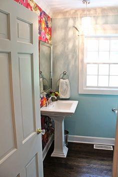 Dramatic wallpaper helps make a small space cozy, but if the wallpaper is really loud, use the bold wallpaper on one wall and a solid color for the remainder of the space. We love how the Blazing Wallpaper from Anthropologie is paired with a turquoise paint color in this powder room. The printed wallpaper becomes the focal point of the space. #bath #design #smallspaces