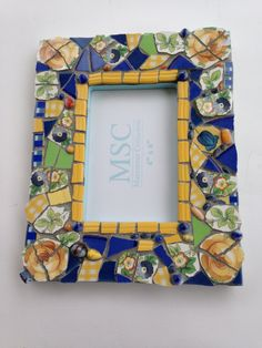 Handmade mosaic frame in blue yellow and green by RPMosaics, $20.00