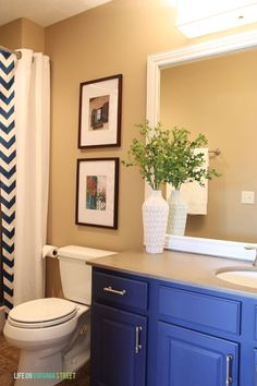 Builder basic bathroom makeover. SO many DIY projects including chalk paint painted cabinets, framed out mirror and no-sew shower curtain!