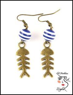 Boucle d'oreille bronze squelette de poisson et perles rayés bleu et blanche marine en résine .(métal couleur bronze) Elles mesurent 6cm de longue.  Existe en bijoux assortie - 17210021