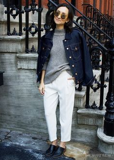 A Joe Fresh denim jacket is worn with a gray Theory sweater, white pants and black mules. Sunglasses are Steven Alan Women's Amity Sunglasses in apricot.