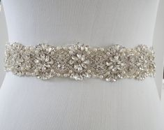 This stunning vintage inspired bridal sash is embellished with pearls and high quality glass crystals. The embellishment is 2 wide x length is available in 14, 17.5 and 25. The sash is made with double faced satin ribbon 1.5 wide and is 3 yards long. Beautiful addition to your wedding gown. PROCESSING: Please allow 3-5 business days for production. Also be sure to leave the date you require your order or your wedding date. For rush order, please convo us before placing your order.  SHIPPING…