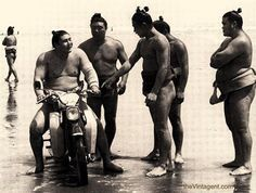 A group of Sumo wrestlers test out a Honda Super Cub on the beach. (ca. 1960)