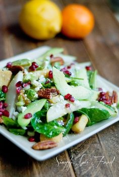 Looks like Spinach, walnuts, craisins, green apples, avocados, pomegranate seeds, and croutons with feta?  YUM.