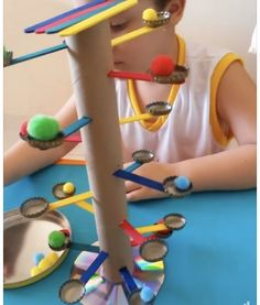 "Home made fine motor toy. Use tweezers to place the pom-poms on the tree ""branches"""