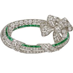 Art Deco Emerald Diamond Platinum Ribbon Brooch | From a unique collection of vintage brooches at https://www.1stdibs.com/jewelry/brooches/brooches/