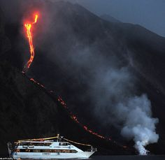 Eruption: A tourist boat sails close tot he action so holidaymakers can watch on as lava from the Stromboli volcano flows into the Mediterranean Sea