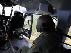 A Border Patrol agent points out an area of possible illegal activity to a National Guard aviator along the Texas-Mexico border July 17, 2013. National Guardsmen from across the country assist Customs and Border Protection in disrupting transnational criminal organizations and drug trafficking organizations by conducting aerial detection and monitoring along the U.S.-Mexico border in support of Operation Phalanx and the U.S. Department of Homeland Security. To ensure continuity of mission, a…