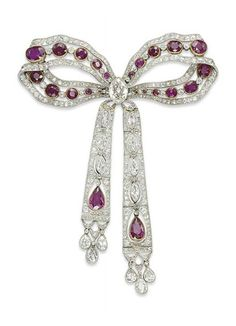A BELLE EPOQUE RUBY AND DIAMOND BROOCH, BY KOCH   Designed as a ruby and diamond openwork bow, centering upon a marquise-cut diamond, to the two ruby and diamond tassels, mounted in platinum, circa 1910, 9.5 cm  Signed Koch
