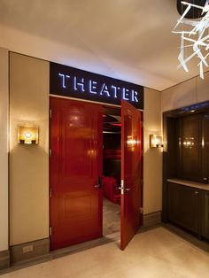 """Substantial wood doors and a neon-lit marquis make for an appropriate entryway to this luxury home theater. Prior to the home's overall architectural design, the homeowner worked with a specialist in creating a no-compromise home theater. He then instructed his architect to design a home """"around the theater."""""""