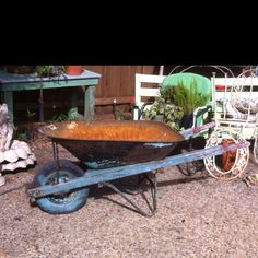 Love to use old wheel barrows in the garden.  Fill them with annuals that overflow the barrel.  There are rose bushes that will do this, now.  Would love a combination of palest pink to salmon roses in this.  Or white to a variegated cream colors.  Country garden romance!