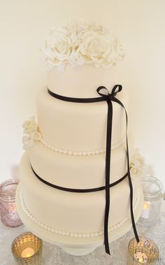 Emily A classic and elegant ivory finished four tier wedding cake with hand…
