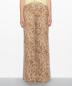 Airy silk shapes a drapey pair of pants that fits like a dream. Neutral hues balance the edgy snake-and-skull print that patterns this pair.Measurements (size S): 34'' inseam; 12.5'' rise100% silkDry cleanImported
