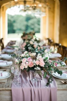 A romantic pale pink and purple wedding tablescape. The draped tablecloth warms the light wood table underneath. The table is adorned with crystal glasses and luscious bouquets.