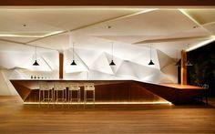 meuble-bar-design-Nosotros-bois-sucupira-éclairage-led-indirect-mur-facetté meuble bar design