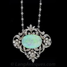 Edwardian Opal and Diamond Necklace, A lovely 5.50 carat oval white opal cabochon is framed by garlands and floral motifs set with old mine cut diamonds in platinum over 18 karat yellow gold. This Edwardian gem is show on a platinum 18 inch diamond set chain. by wteresa