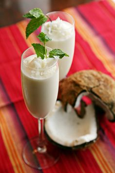 Piña Colada -  (Makes about 2 drinks)  INGREDIENTS:  2 ounces coconut rum  1 ounce banana liqueur  2 ounces pineapple juice  1 fresh ring of pineapple, cubed  1 cup crushed ice  Coconut shavings and mint, for garnish