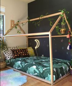 deco-méthode-montessori-chambre-enfant-lit-maisonnette-en-bois-taies-d-oreiller-multicolores-couverture-matelas-palmier-mur-d-accent-noir-parquet-clair-guirlande-lumineux