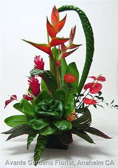 Heliconias, ginger, anthuriums, orchid, proteas and woven palm foliages were used to create this tall and stately presentation.