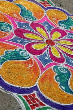 In India, there is a long-standing folk art known as rangoli (or kolam or Muggu), in which patterns are created on the floor using materials such as colored rice, dry flour, and more. The bright designs are usually made during auspicious events like Diwali, Onam, Pongal, and other Indian festivals. You'd also see them during wedding celebrations, and their presence is considered sacred welcoming areas for the Hindu deities. Rangoli is meant as decoration and thought to bring good luck. The…