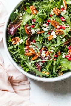 This beautiful, delicious fall or winter salad is made with mixed baby greens, pomegranate, gorgonzola and pecans with a pomegranate vinaigrette. #salad