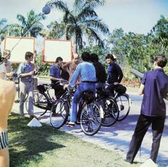 24 March 1965, Interfield Road, Nassau, New Providence, Bahamas Original caption: Nassau, Bahamas: Beatles Ringo Starr, Paul McCartney, George, Harrison and John Lennon astride bicycles as they talk with production crew during filming of their new...
