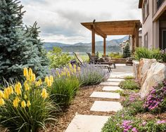 This back yard, Colorado xeriscape blends seamlessly into the Colorado native landscape in the background with views of Red Rocks. A Pergola creates shade and a sense of space, complete with stone