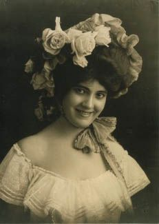"""Woman in peasant blouse and flowered hat, taken at the 1904 World's Fair by the Emme & Mayme Gerhard. The sisters' portraits of the more """"exotic"""" people at the Fair gave them a worldwide audience. They were among the first photographers to capture images of people from all over the world. After the Fair, the Gerhard sisters continued to earn renown because of their unique use of natural light and informal poses to capture the personalities of their subjects. Missouri History Museum"""