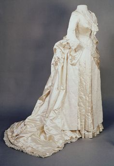 1889 Cream satin Wedding Dress consisting of a jacket bodice, skirt, and train. Made in the UK. Worn by Ella Lewin (née Alston) of Bromley, Kent, the daughter of a well-to-do Ceylon tea merchant, for her marriage in 1889. Via V&A.