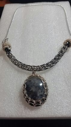 2 tone black and silver viking knit necklace with titanium end caps and a viking knit wrapped moss agate pendant.