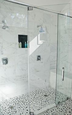 Amazing master bath features a seamless glass shower clad in white marble tiles fitted with his and her shower heads alongside a blue and gray river rock shower floor.