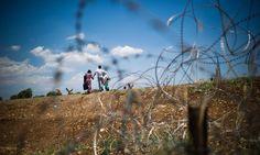 Syrian refugees crossing the Syrian-Turkish border near Marea